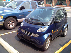 Front and side view of a blue Smart Fortwo in a parking space next to an ordinary pick-up truck by fleur-design on Flickr