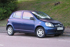 Right side view of a blue Toyota Yaris on the street
