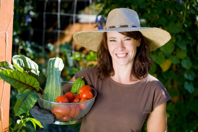 A woman displaying a vegetable harvest from her eco garden
