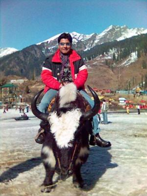 Me riding a Yak in Manali, India, with the backdrop of the Himalayas behind me. I hope they can survive the forces of climate change!